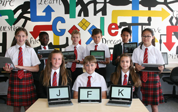 Students holding their new Chromebooks
