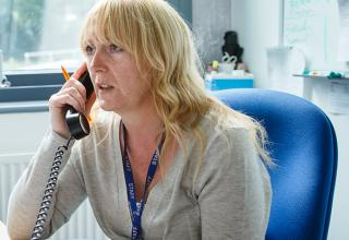 member of school staff on the phone to the service desk