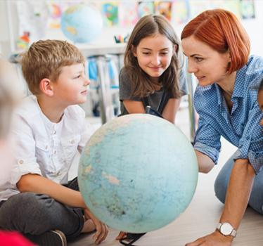 Teacher with children and globe