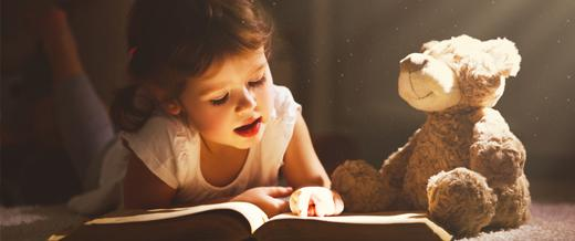 Child reading with teddy