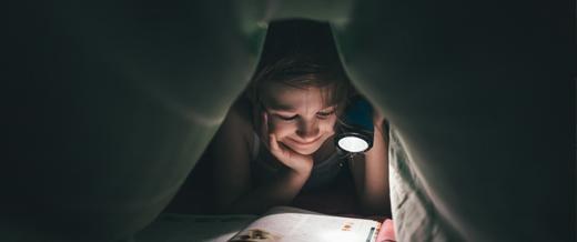 Child Reading in Bed with Torch