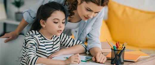 Mother with home schooling child at desk