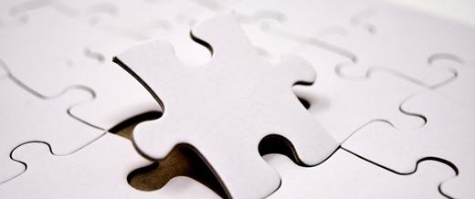 A jigsaw piece rising up from a completed jigsaw set
