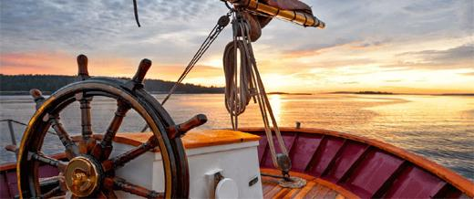 Helm of sailing ship at sunset