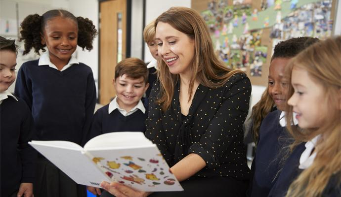 Children reading book with teacher