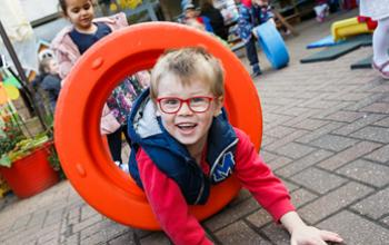 boy playing in outdoor activity equipment