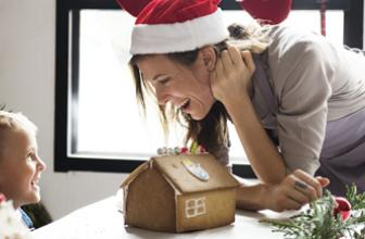 Festive woman with child and gingerbread house