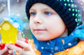 Child in snow with toy object